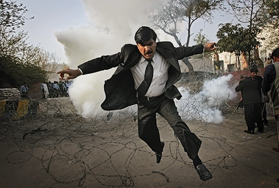 A Pakistani lawyer runs away from tear gas fired by police outside the residence of the country's deposed chief justice, Iftikhar Mahmood Chaudhry, during a protest in Islamabad, Pakistan, on March 9, 2008.