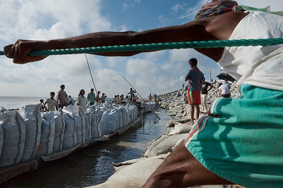 Bangladesh, 2009  Bangladeshis in Sirajganj haul boatloads of bagged sand to reinforce a levee eroded by the flooding of the Jamuna River. If melting ice swells the area's rivers, such stopgap fixes may become more common.