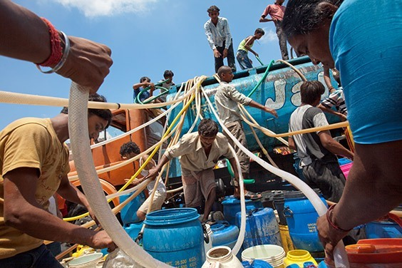 "India, 2009  In a parched Delhi slum, men swarm a tanker to siphon precious water. ""If you throw money here,"" says a local 16-year-old named Vinay, ""no one would have time to grab it. Water is more important for us."""