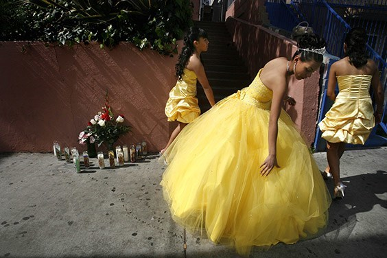 Jessica Alvarado fixes her Quinceañera dress on a blood-stained sidewalk next to a memorial honoring tamale vendor Cosme Gonzaleza, who was robbed and killed in front of her Los Angeles home.