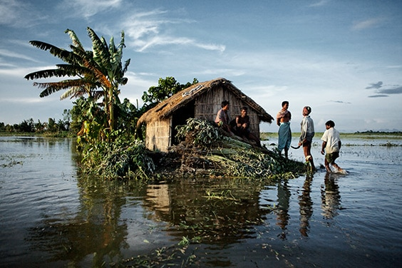 Gaibandha District, Bangladesh, 2010. During the harvest of jute, villagers rest above the floodwaters of the surging Brahmaputra River. A simple adaptation in flood-prone areas is building every house on a two-meter tall mud plinth.